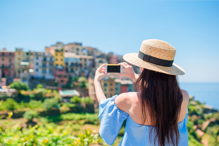 Young woman take a photo of beautiful view at old village in Cinque Terre, Liguria, Italy. European italian vacation. Stock Photo