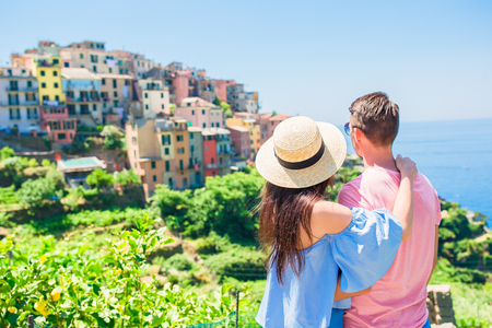Happy couple with beautiful view of old coastal village in Cinque Terre national park, Liguria, Italy ,Europe
