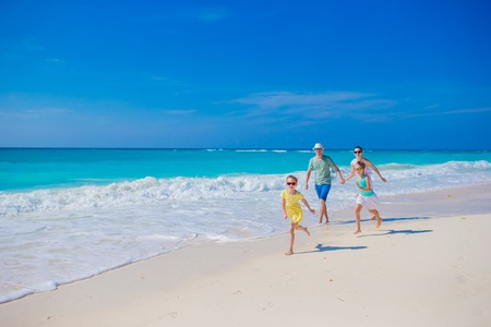 Family on white tropical beach have a lot of fun. Father and kids enjoy holidays on the seashore Imagens