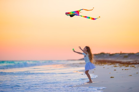 Little girl with flying kite on tropical beach at sunset. Kid play on ocean shore. Child with beach toys.