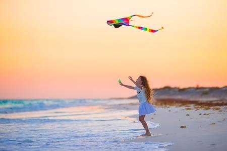 Meisje met vliegende vlieger op tropisch strand bij zonsondergang. Kid spelen op oceaan kust. Kind met strand speelgoed. Stockfoto