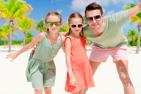 yahoo: Father and little girls having fun on white beach in palm grove