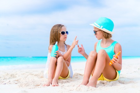sunburnt: Kids applying sun cream to each other on the beach. The concept of protection from ultraviolet radiation Stock Photo
