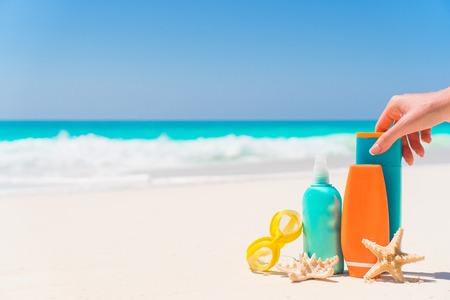 Suncream bottles, goggles, starfish on white sand beach background ocean Stock Photo