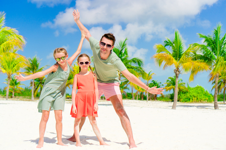 yahoo: Father and little daughters having fun on white beach in palm grove. Family vacation