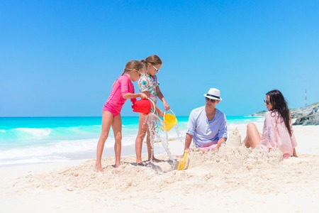 Family of four making sand castle on their beach vacation Stock Photo