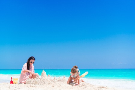 Mother and little kid making sand castle at tropical beach Stock Photo