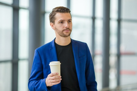 Young man with coffee inside in airport while waiting for boarding. Casual young boy wearing suit jacket. Stock Photo