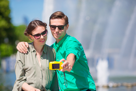 Couple taking a selfie background the fountain. Young man making photo of woman on the street laughing and having fun in summer.