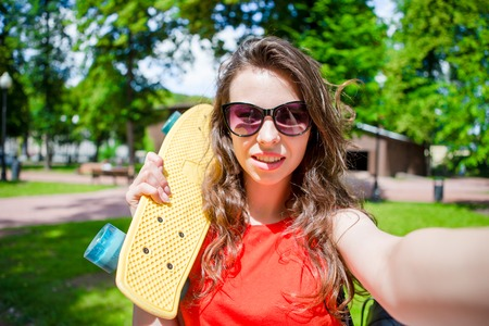 Young girl having fun with skateboard in the park. Lifestyle portrait of young positive woman having fun and enjoy warm weather. Stock Photo