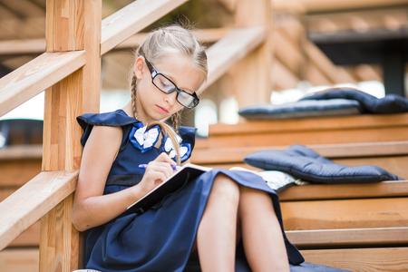 Adorable petite fille de l & # 39 ; école avec des notes et des crayons à l & # 39 ; extérieur . Banque d'images - 84799680