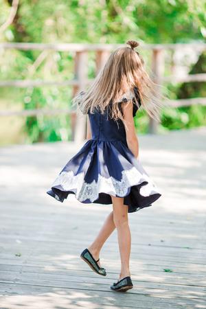 Adorable little school girl have fun outdoor. Back to school.