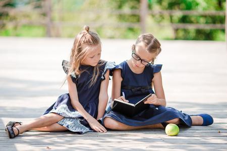 Adorables petites filles de l'école avec des notes et des crayons en plein air. Retour à l'école. Banque d'images - 84798882