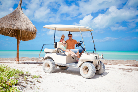 Young father and two little kids driving golf cart on a tropical beach