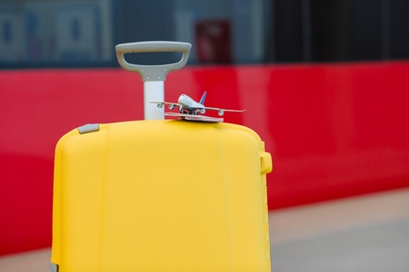 Closeup red passports and airplane small model on yellow luggage at train station