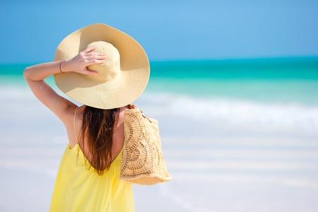 Vue arrière de la femme au chapeau pendant les vacances de plage tropicale