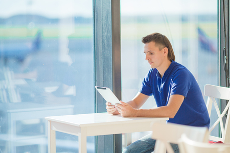 Young man in an airport lounge waiting for flight aircraft. Stock Photo