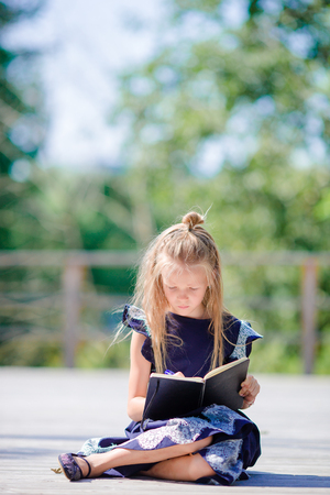 Adorable little school girl with notes and pencils outdoor. Back to school. Stock Photo