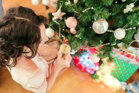 Happy young woman on Christmas eve near festive fir-tree Stock Photo