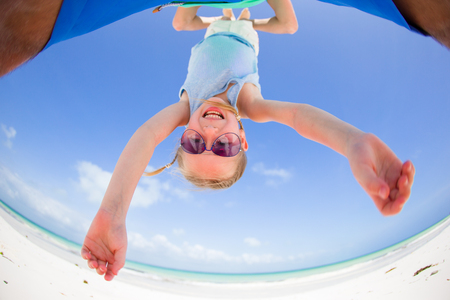 Little girl outdoors during summer vacation have fun with father. Portrait of a kid upside down on a sky background Stock Photo