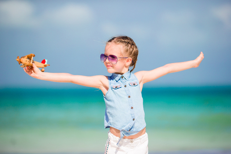 Happy little girl with toy airplane in hands on white sandy beach Stock Photo
