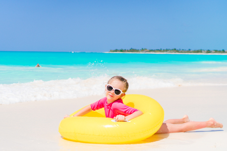Happy little girl with inflatable rubber circle having fun on the beach