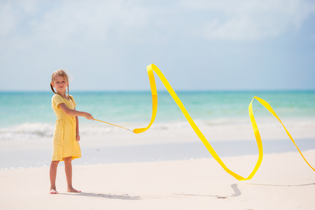 Adorable little girl dancing with yellow gymnastic ribbon on the beach