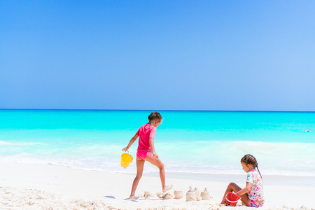 Adorable little girls during summer vacation. Kids playing with beach toys on the white beach