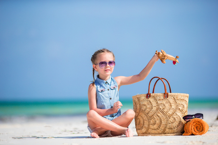 Happy little kid with toy airplane in hands on white sandy beach Stock Photo
