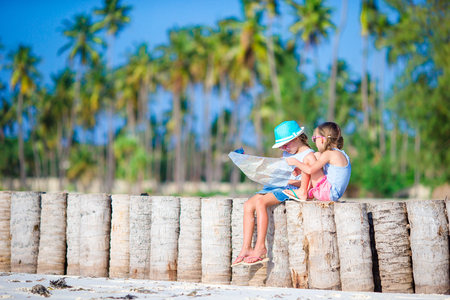 2 way: Adorable little girls with big map of island on beach