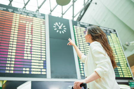 Young woman in international airport looking at the flight information board checking for flight