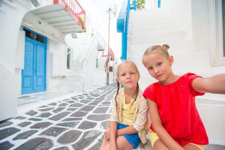 Two little girls taking selfie photo outdoors in greek village on narrow street in Mykonos Stock Photo