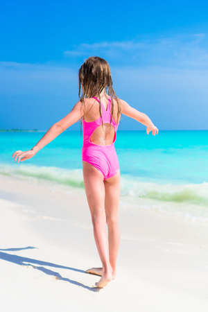 Adorable little girl in swimsuit on beach vacation 스톡 콘텐츠