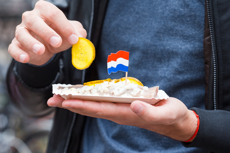 Fresh herring with onion and netherland flag in male hands closeup. Traditional dutch food