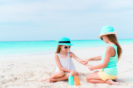 Kids applying sun cream to each other on the beach. The concept of protection from ultraviolet radiation Stock Photo