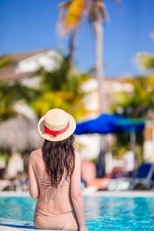 Beautiful young woman relaxing on the edge of infiniti pool