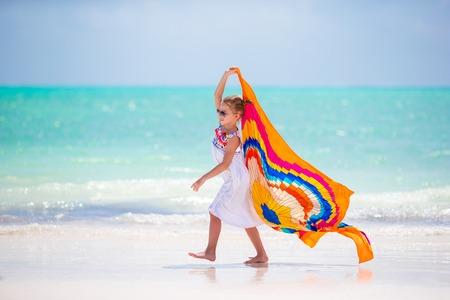 Little girl hve fun on the beach. Kid enjoy beach vacation with pareo