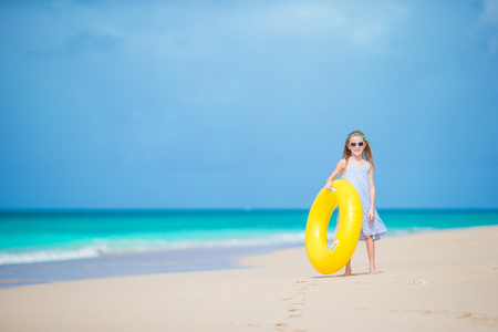 Adorable girl with inflatable rubber circle on white beach ready for swimming Stock Photo