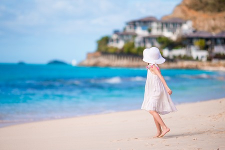 Little girl in hat at the beach during caribbean vacation