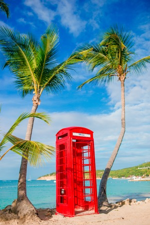 Red phone booth in Dickensons bay Antigua. Beautiful landscape with a classic phone booth on the white sandy beach in Antigua Stock Photo