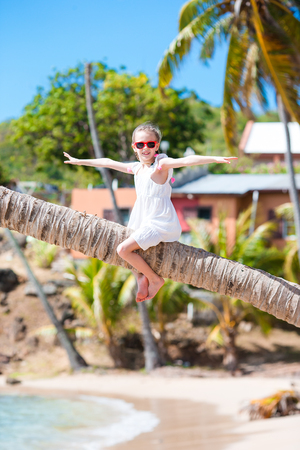 Happy kid sitting on palm tree during caribbean vacation on white beach