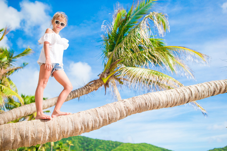 adorable little girl at tropical beach on palm tree during summer vacation background of blue sky