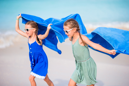 Cute little girls having fun running with towel and enjoying vacation on tropical beach with white sand and turquoise ocean water Standard-Bild