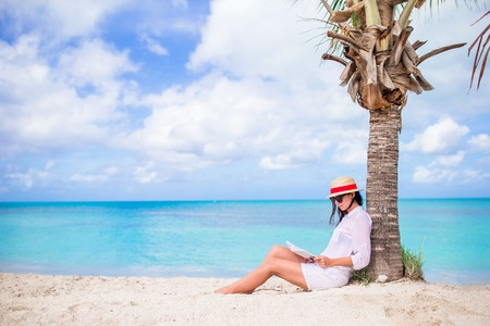 Young woman reading book during tropical white beach Banque d'images
