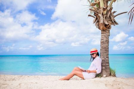 Young woman reading book during tropical white beach Foto de archivo