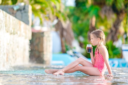 Little girl in outdoor swimming pool enjoy her vacation with tasty drink Foto de archivo