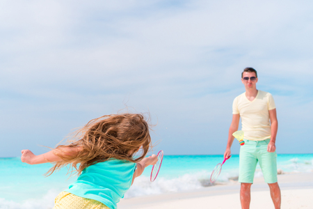 Little girl playing tennis with father on white tropical beach