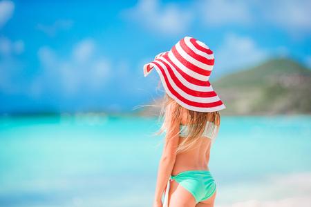 Adorable little girl in big hat walking along white sand Caribbean beach Standard-Bild
