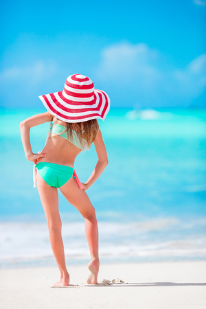 Adorable little girl in big hat on white sand Caribbean beach