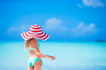 Adorable little girl in big hat walking along white sand Caribbean beach Stock Photo